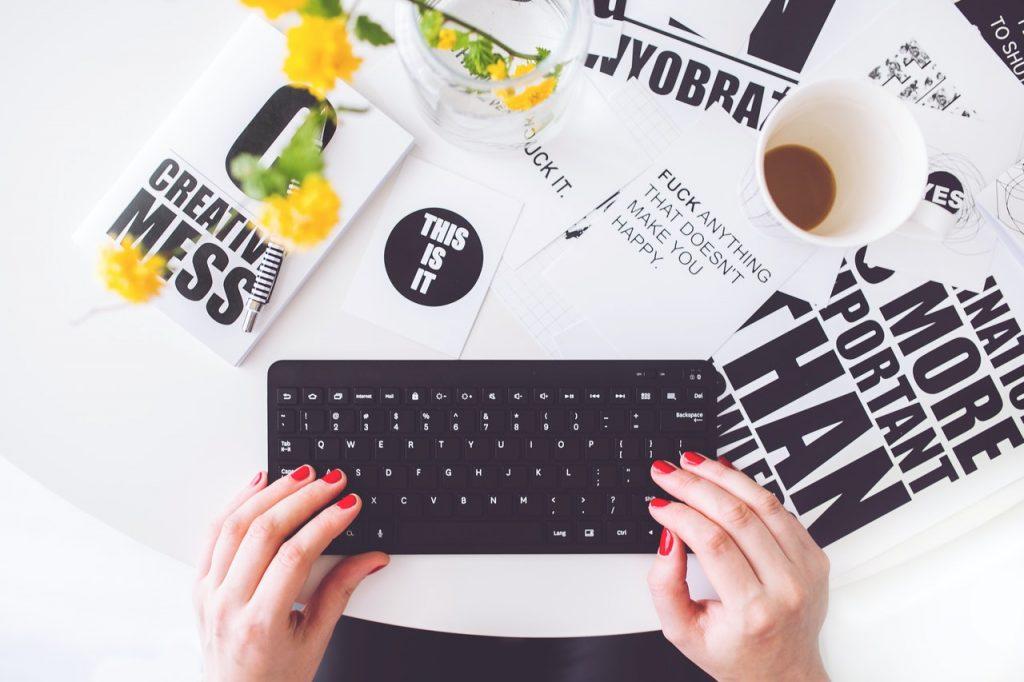Femme avec du vernis rouge écrivant sur son clavier d'ordinateur sur une table avec de la presse papier