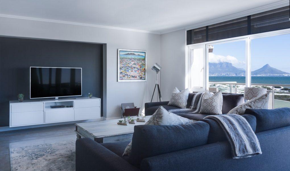 Salon avec canapé bleu marine, baie vitrée avec vue