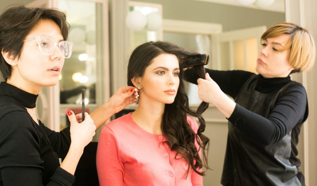 Deux coiffeuses coiffant une femme brune