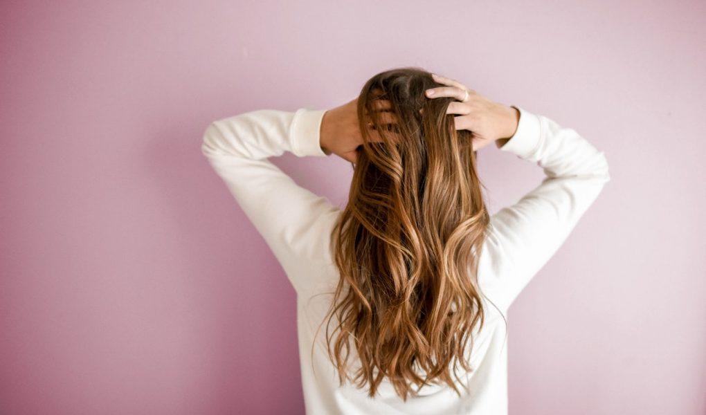 Femme de dos tenant ses long cheveux blonds ondulés entre ses mains