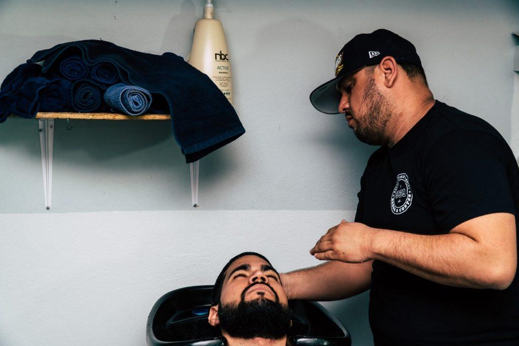 Homme se faisant faire un shampoing dans un bac par un coiffeur