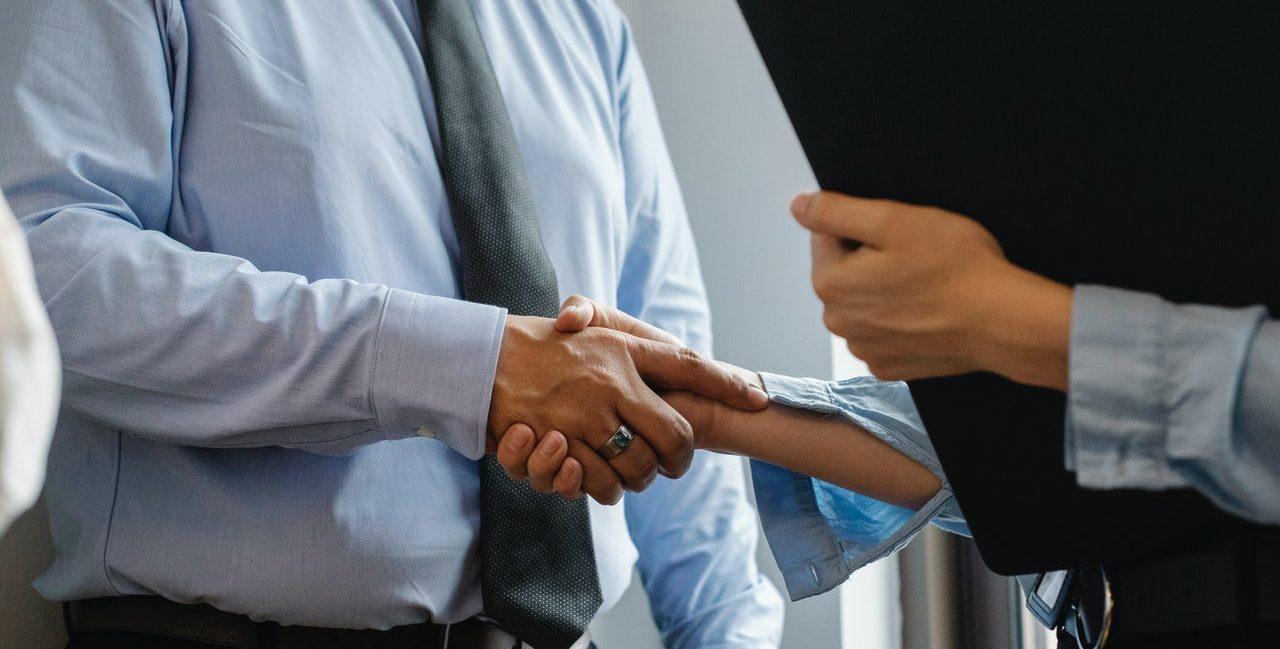 Homme portant une chemise et une cravate, serrant la main