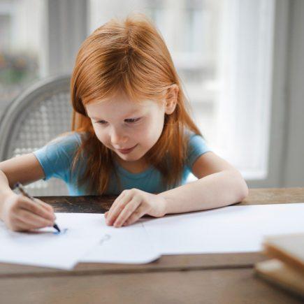 Petite fille dessinant sur son bureau